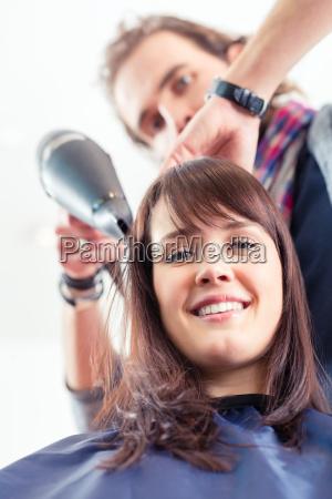 friseur foehnt frau die haare im