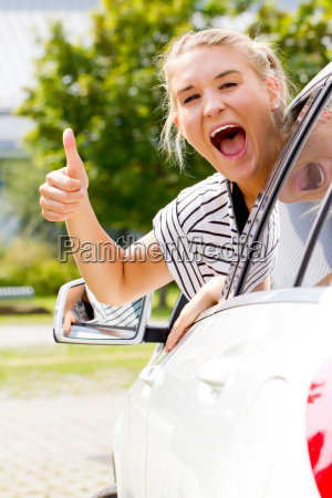 young female driver with thumb up