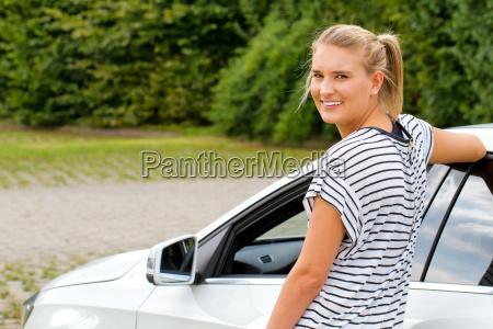 junge frau vor ihrem auto