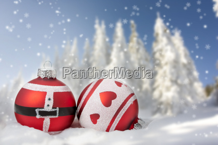 weihnachtskarte mit weihnachtskugeln und verschneiten baeumen
