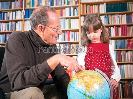 grossvater und enkeltochter betrachten einen globus