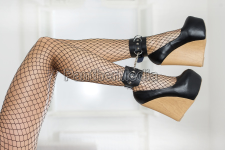 legs in fishnet stockings ankle cuffs