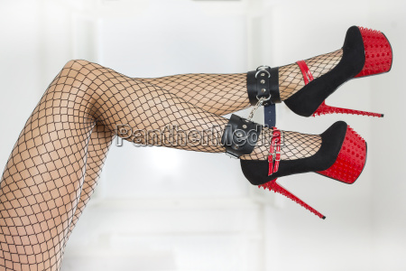 legs wearing fishnet stockings ankle cuffs