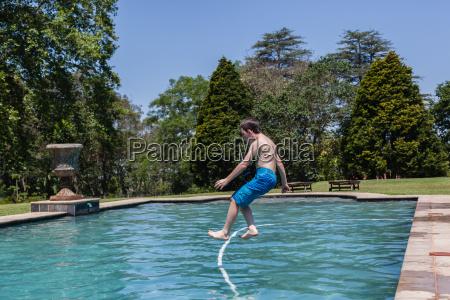 boy jumping pool