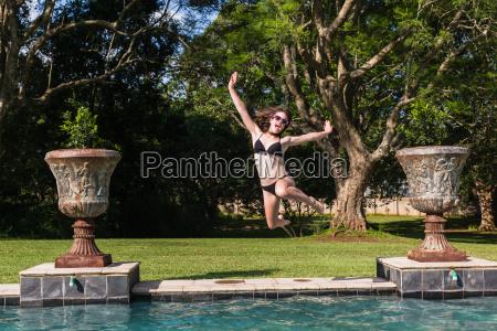 girl jumping swimming pool