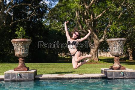 girl jump swimming pool
