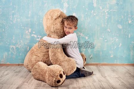 kind kuschelt mit teddybaer