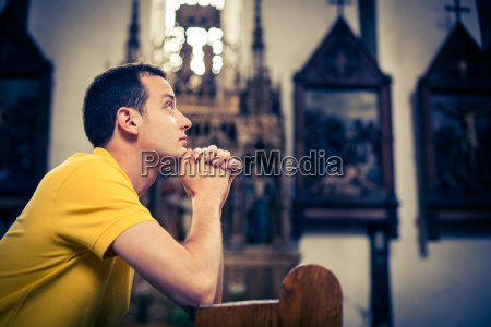 gut aussehender junger mann beten in