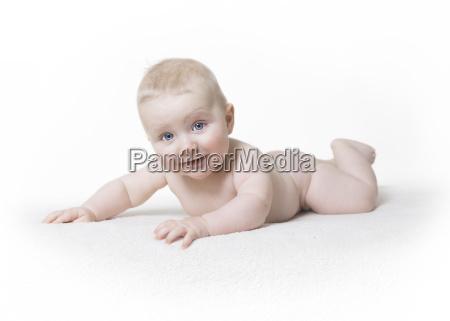 naked baby laughing at the camera