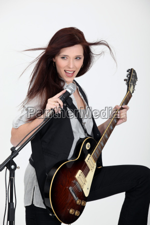 young woman playing guitar and singing