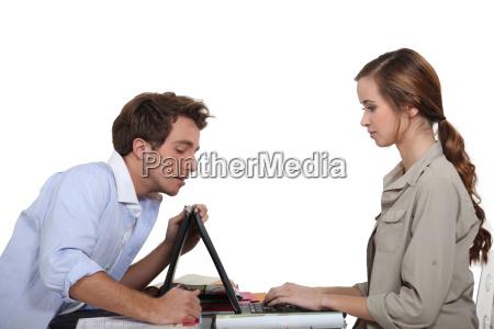 man hilft frau mit laptop