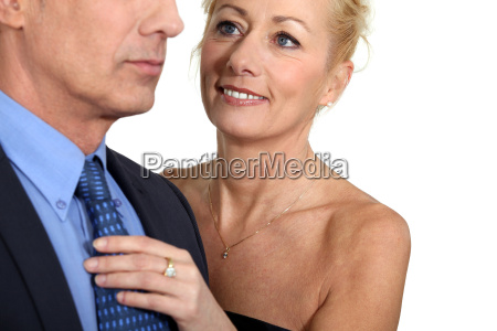 wife helping husband with tie