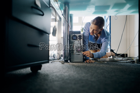 young secretary connecting cables to pc