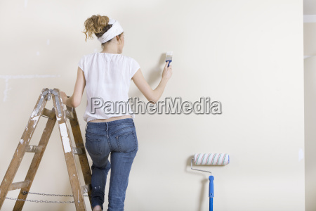 woman stroking wall on ladder
