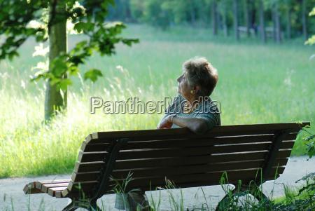 seniorin sinniert auf parkbank