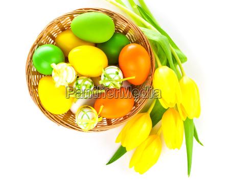 korb mit ostereiern und gelbe tulpen