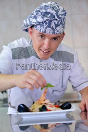 koch bereitet essen zu