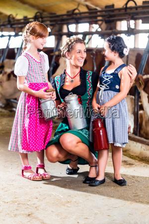 bayrische familie mit milchkannen im kuhstall