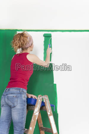 woman on ladder sweeps wall green