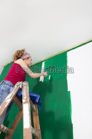 woman paints wall green