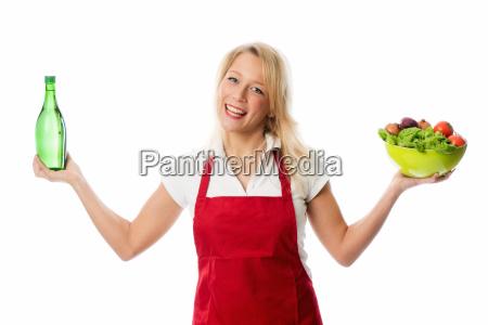 a woman presenting a bowl salad