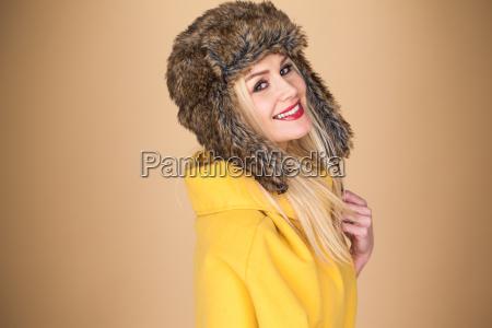 ziemlich laechelnde blonde frau im winter