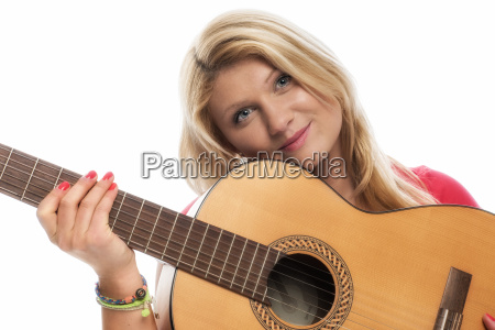 young blonde woman playing guitar and