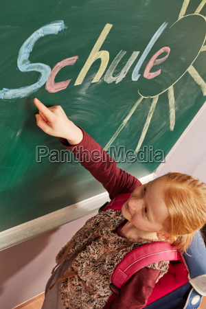 girl pointing to the blackboard