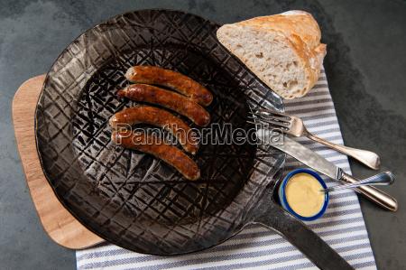 rostbratwürste, mit, sauerkraut, in, einer, pfanne - 13550004