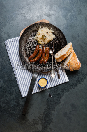 rostbratwürste, mit, sauerkraut, in, einer, pfanne - 13550010
