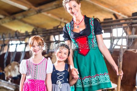 bayrische mutter zeigt kindern kuehe im