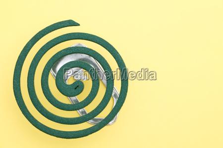 gruen moskitospirale auf gelbem hintergrund