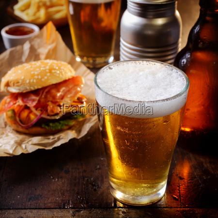 glas gekuehltes bier mit einem hamburger