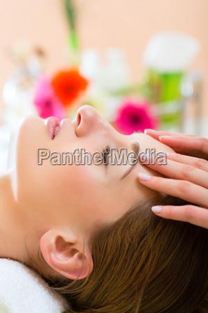 wellness frau erhaelt kopfmassage in