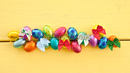 colorful chocolate eggs on yellow