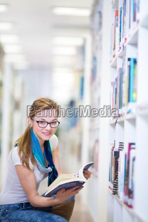 huebsche studentin in einer bibliothek auf