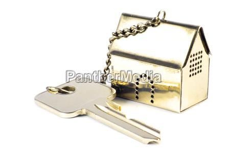 hausschluessel mit einem goldenen musterhaus als