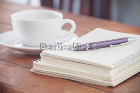 rohes notebook mit stift auf holztisch