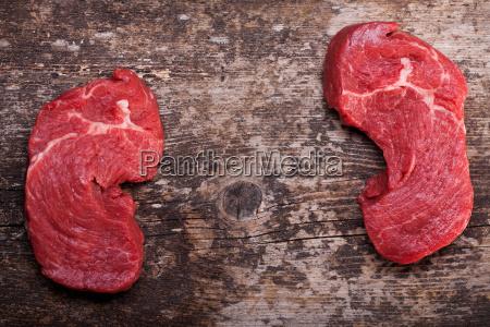 zwei rohen steaks auf ein holzbrett