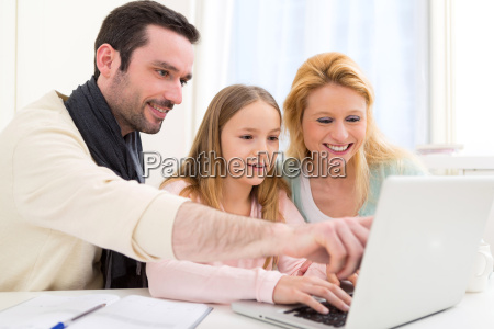 glueckliche familie die vor einem laptop