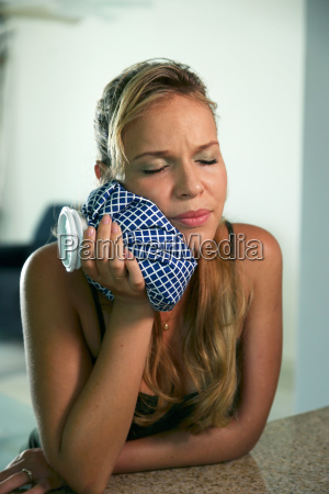 young woman with toothache holding ice