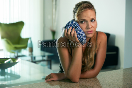 young woman with toothache putting ice