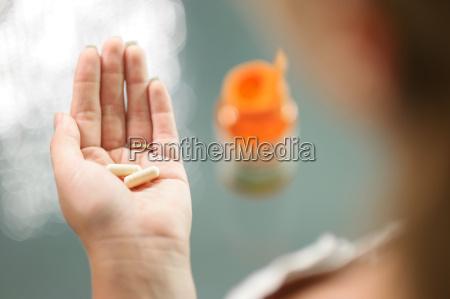 young woman taking vitamins ginseng calcium