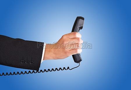 hand des geschaeftsmannes mit telefonhoerer