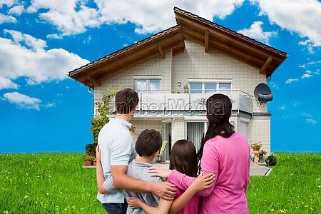 junge familie vor ihr traumhaus stehen