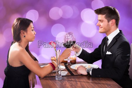 couple toasting wineglasses at restaurant