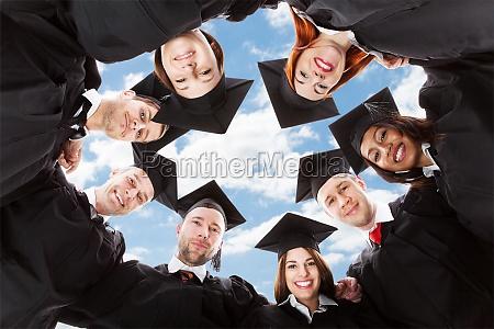 absolwentow stojacych w kregu pochylony w