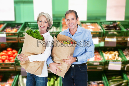 mature couple holding grocery