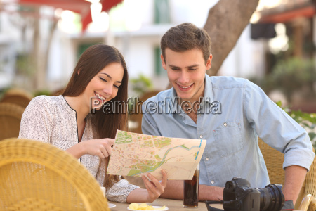 couple tourists consulting a guide in