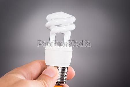 hand die energiesparende gluehlampe haelt